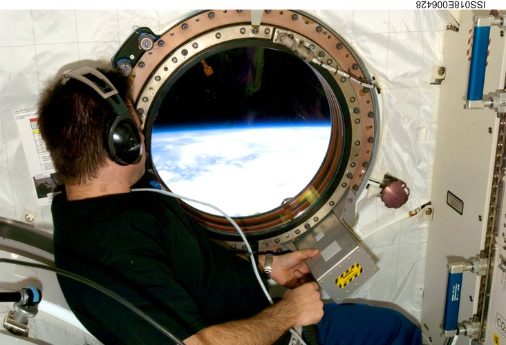 Looking through the window in the Kibo laboratory of the ISS