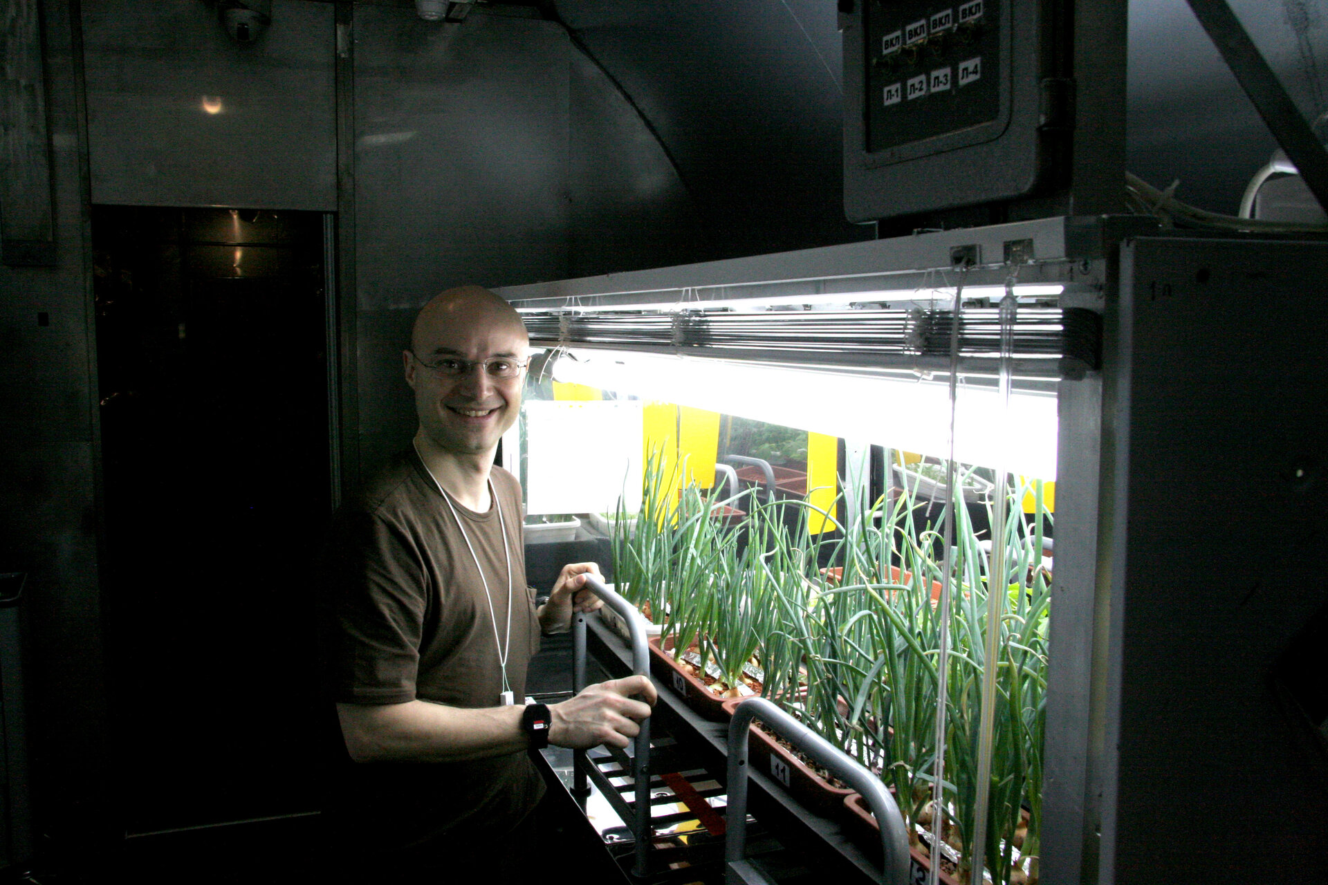 Cyrille with the crops growing in the facility's greenhouse