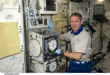 Frank De Winne works on a facility in the Kibo laboratory