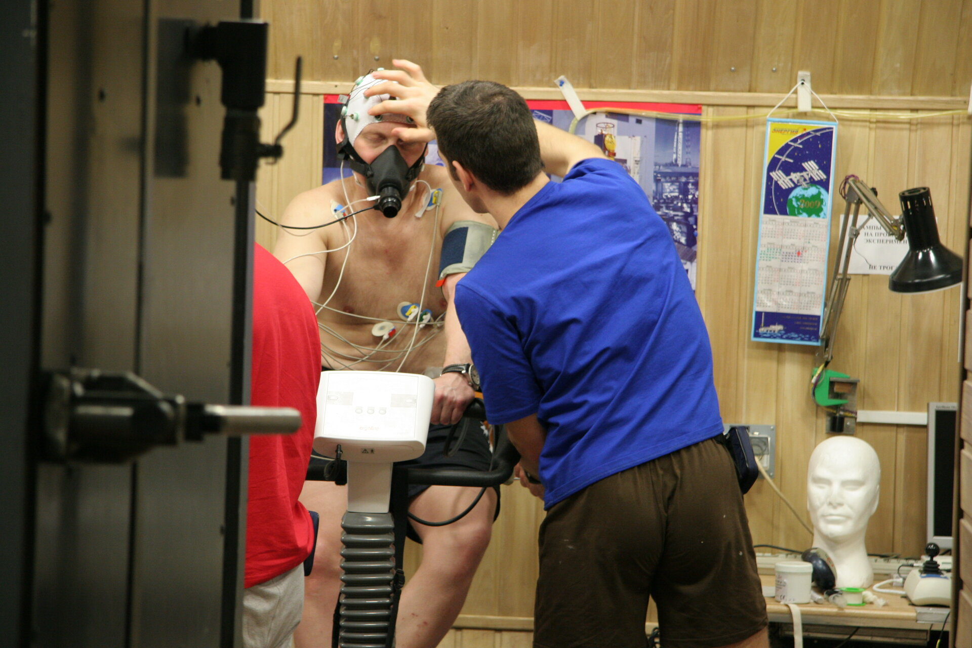Oliver checks electrodes being used to measure brain activity as Oleg exercises on bicycle ergometer