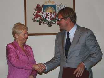 Latvian Minister for Education and Science, Tatjana Koke, and ESA's Peter Hulsroj sign the Cooperation Agreement