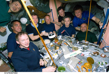 Astronauts and cosmonauts from Expedition 20 and STS-127 share a meal on the ISS