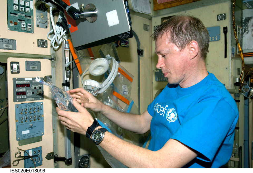 Frank De Winne collects water samples for inflight analysis