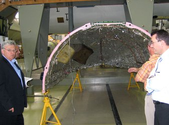 Team members viewing the fairing half-shell