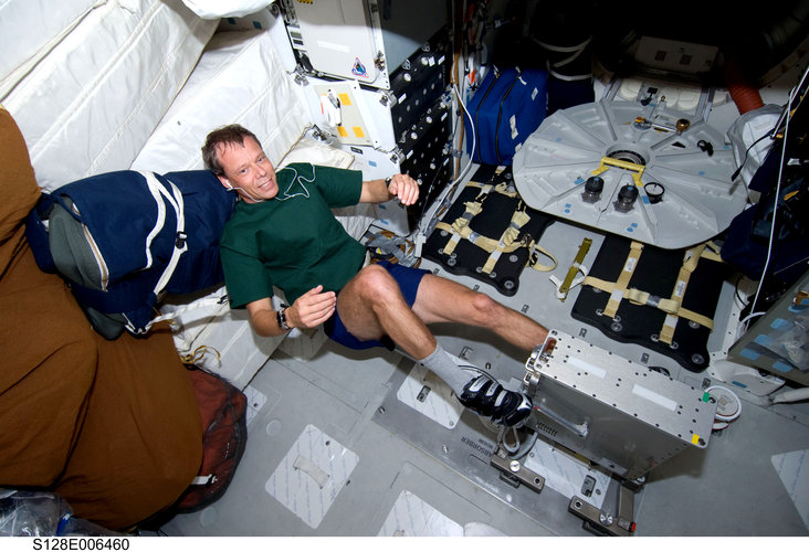Christer Fuglesang exercises on a bicycle ergometer on Shuttle middeck