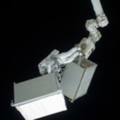 Fuglesang rides the Station's robotic arm