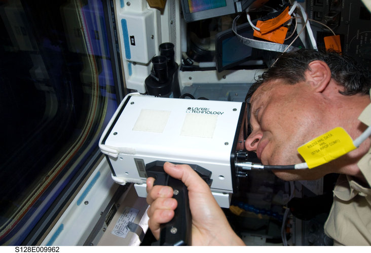 Christer Fuglesang uses handheld laser ranging device after undocking of Discovery from ISS