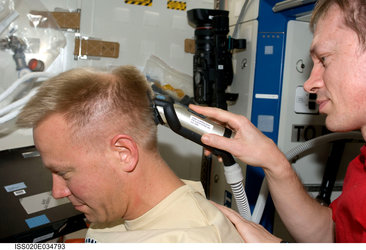 Frank De Winne cuts Tim Kopra's hair using hair clippers fashioned with a vacuum device
