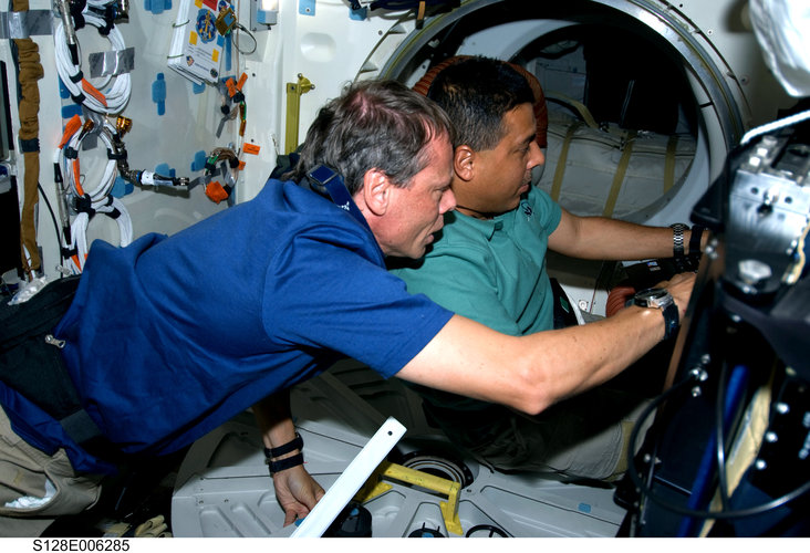 Fuglesang and Hernandez work on Shuttle middeck