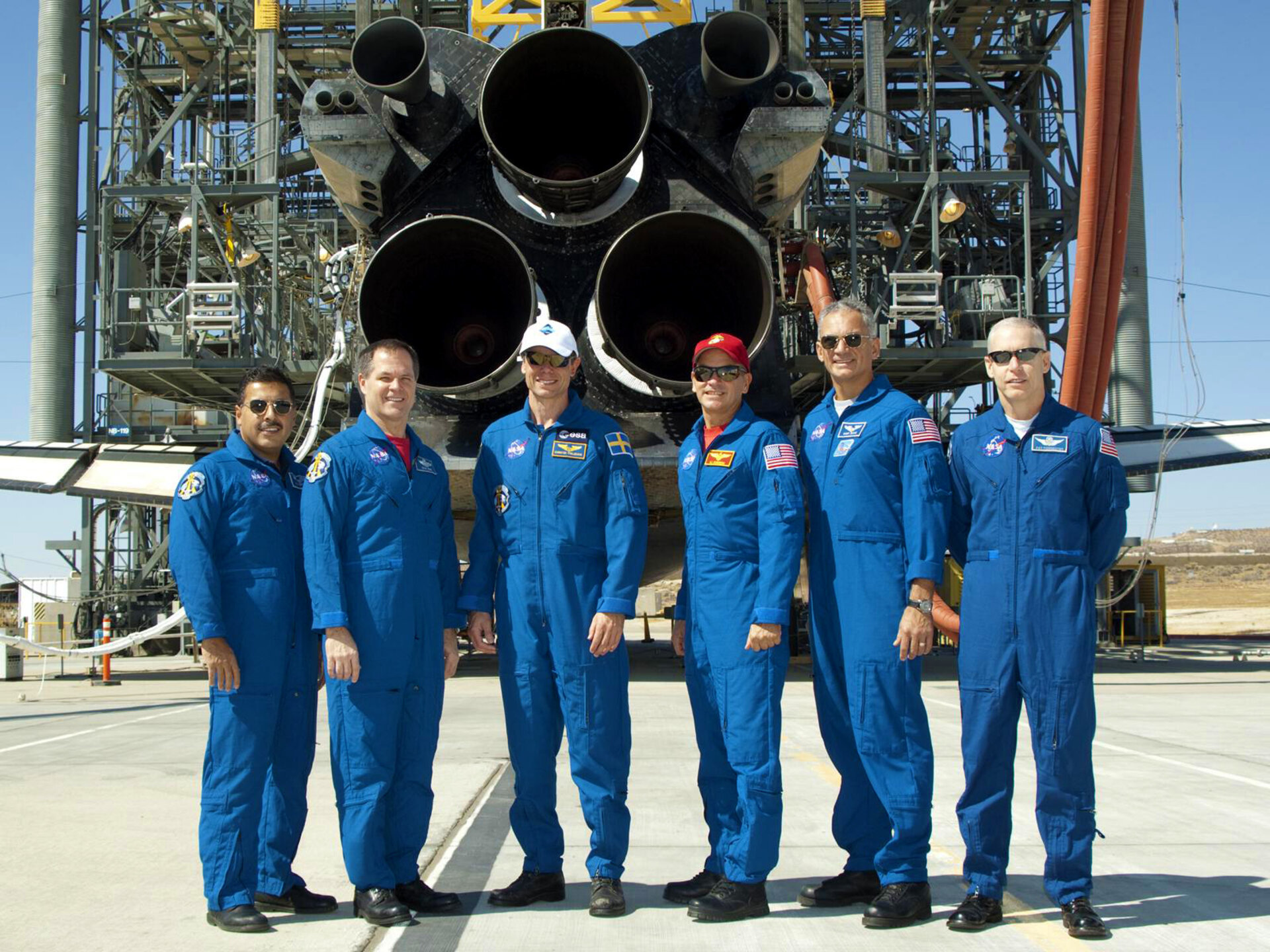 STS-128 crew line up behind Discovery