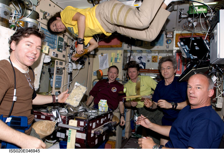 Expedition 20 and 21 crewmembers share a meal in the Zvezda module