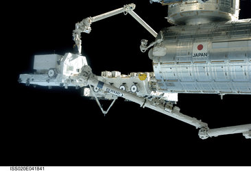 Exposed Pallet is handed off between the Japanese robotic arm and the Station robotic arm