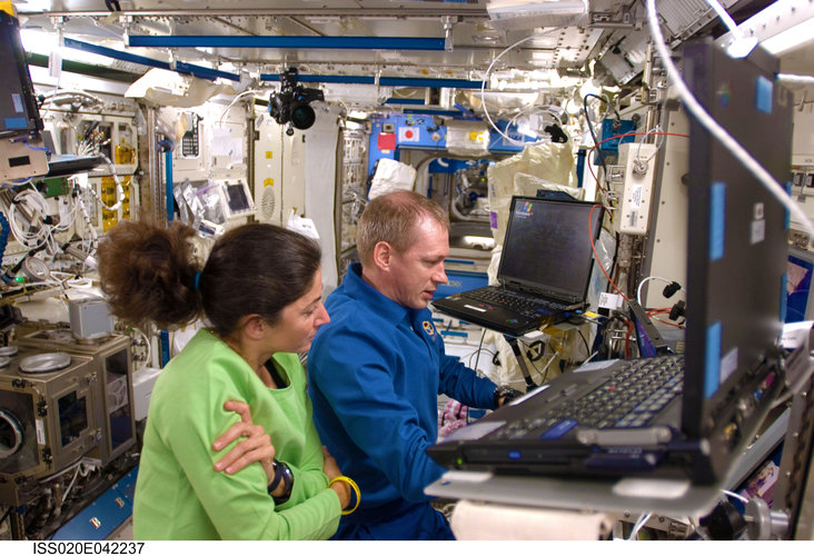 Frank De Winne and Nicole Stott at the controls of the Japanese robotic arm