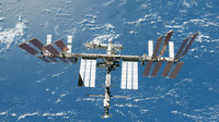 ISS backdropped by a blue and white part of Earth