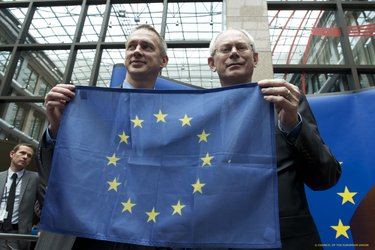 Frank De Winne and Herman van Rompuy with a spacefaring EU flag