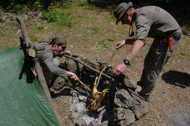 Tim Peake (right) preparing dinner on the campfire