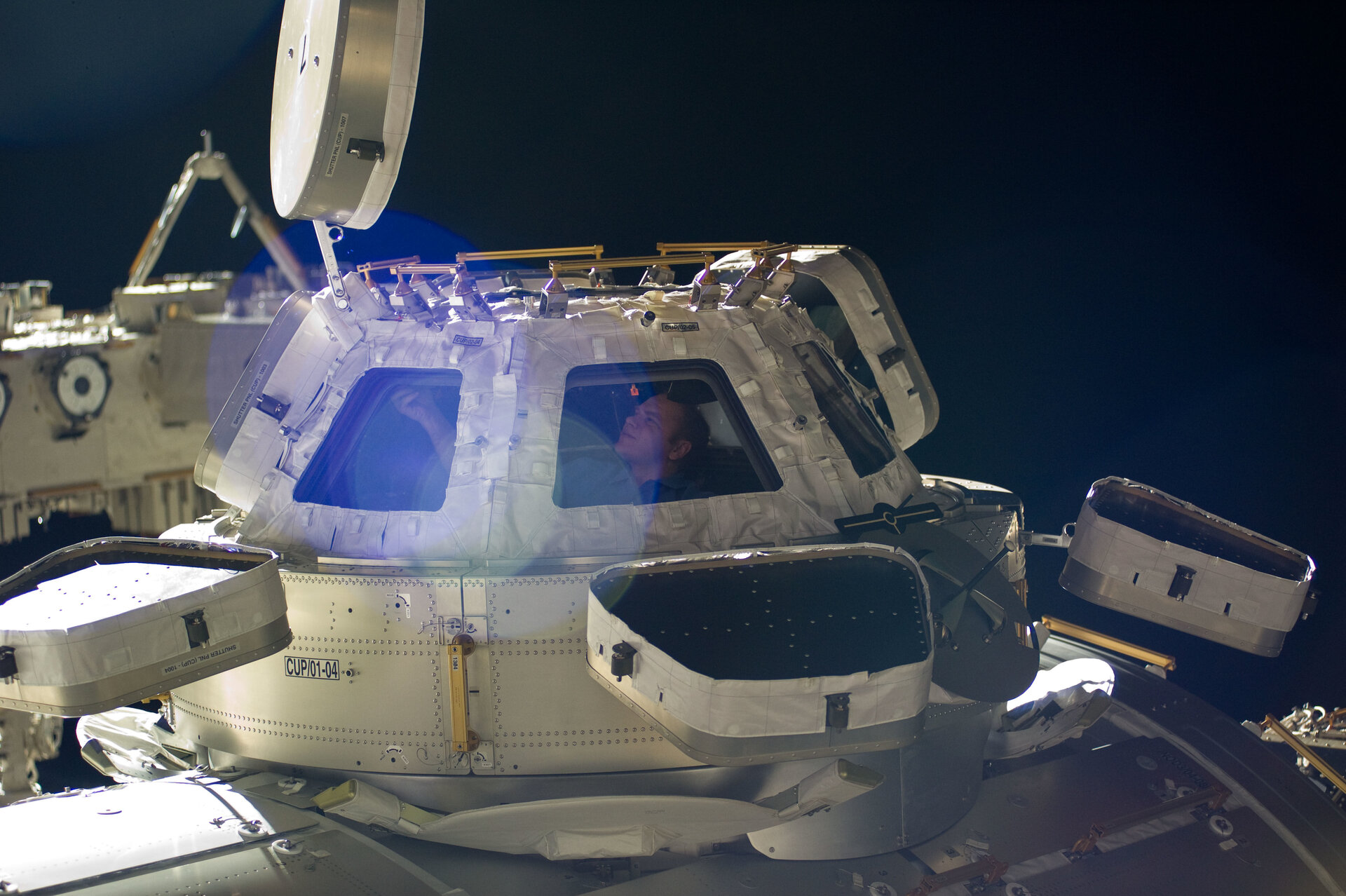 Oleg Kotov in a window of the Cupola