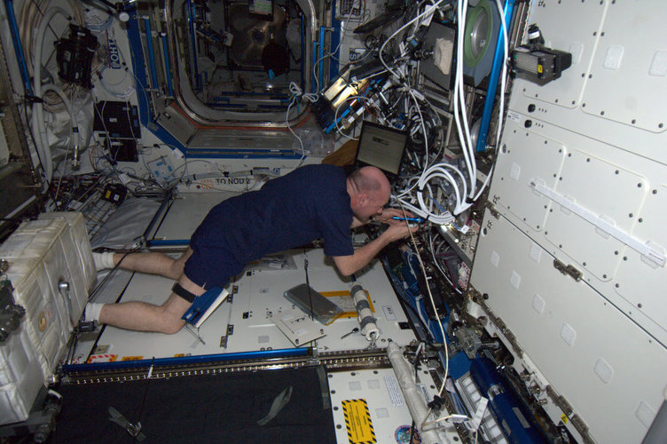 Andre Kuipers changing electronic module in ESA's Microgravity Science Glovebox