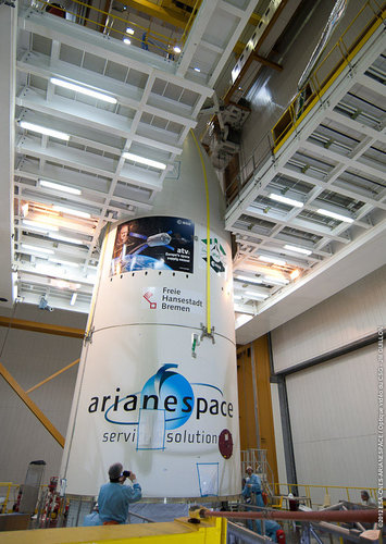 Aerodynamic fairing being lifted by crane over top of ATV-3 in Kourou