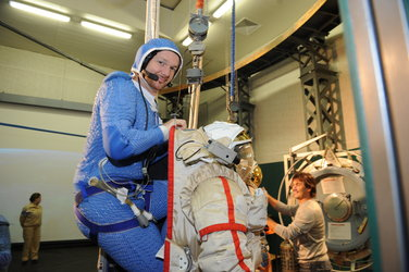 Alexander climbing into his spacesuit
