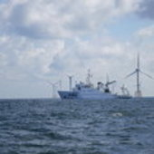 Ship beside wind farm