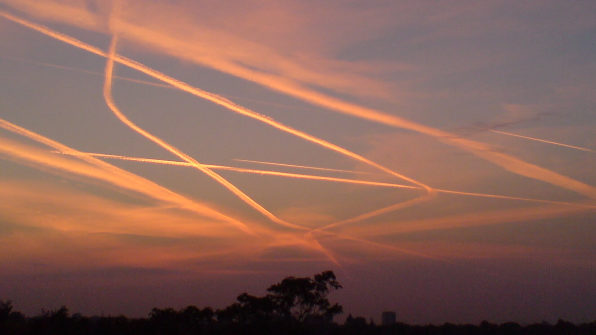 Contrails from air traffic over London's Heathrow Airport
