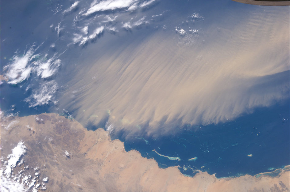 Like a sweeping cloud, a sand storm reaches across the Red Sea