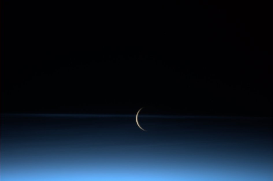 The moon rises surrounded by noctilucent clouds