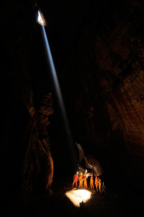 ESA CAVES team standing by a shaft of light deep in the Sardinian caves in Italy.
