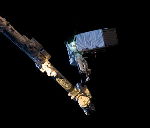 Strapped to a robotic arm holding 385 kg in space at night