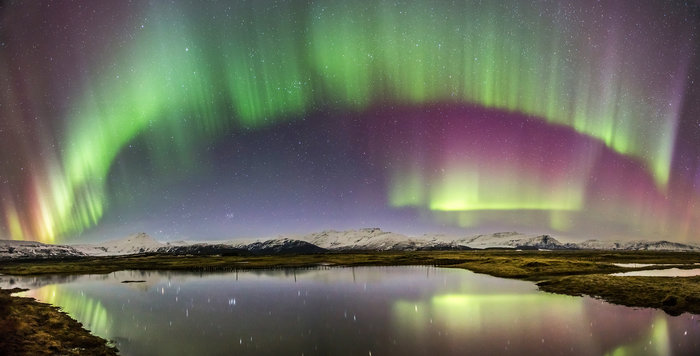 A dramatic panorama shows a colourful, shimmering auroral curtain reflected in a placid Icelandic lake on 18 March 2015 near Jökulsárlón Glacier Lagoon in southern Iceland