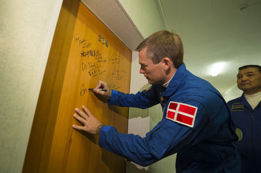 Andreas Mogensen performs the traditional door signing at the Cosmonaut Hotel
