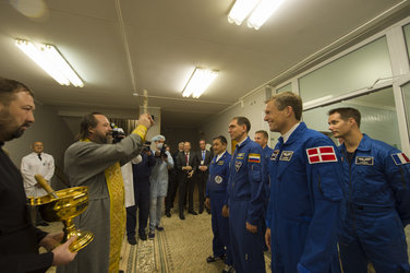 Crew members receive the traditional blessing from a Russian Orthodox priest