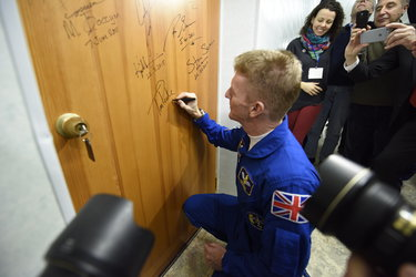 Tim Peake performs the traditional door signing at the Cosmonaut Hotel