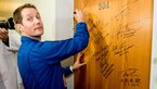 [21/27] Thomas Pesquet performs the traditional door signing at the Cosmonaut Hotel