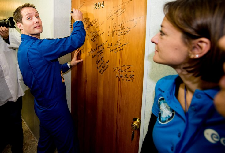 Thomas Pesquet performs the traditional door signing at the Cosmonaut Hotel