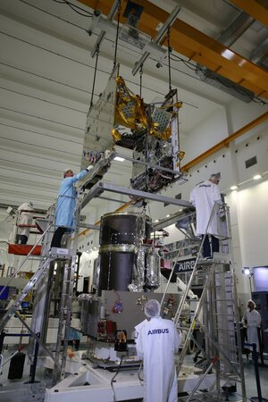 The communications module of Quantum is slowly lowered onto the service module