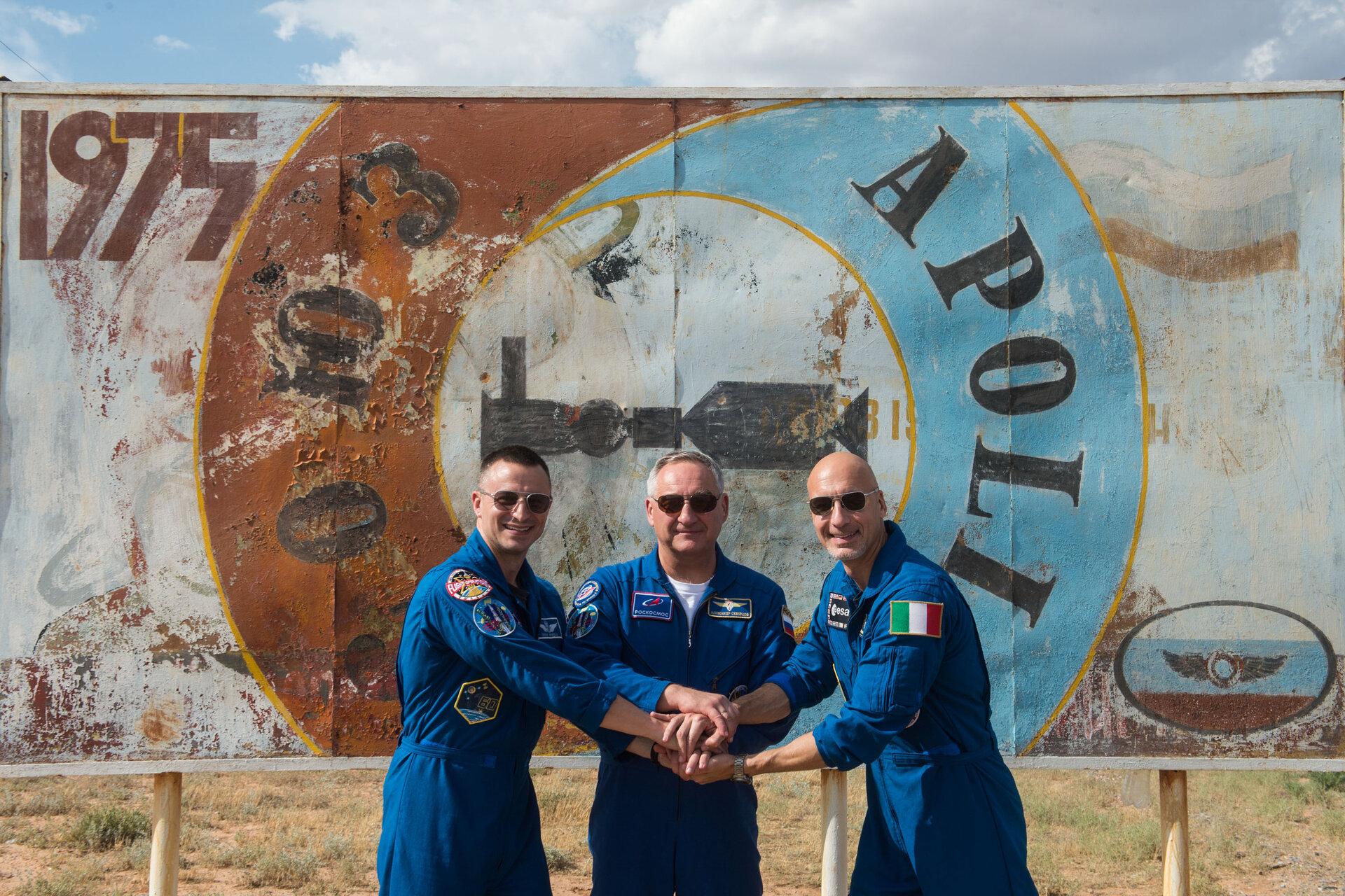 Expedition 60 crewmembers in front of a mural of the 1975 Apollo-Soyuz mission