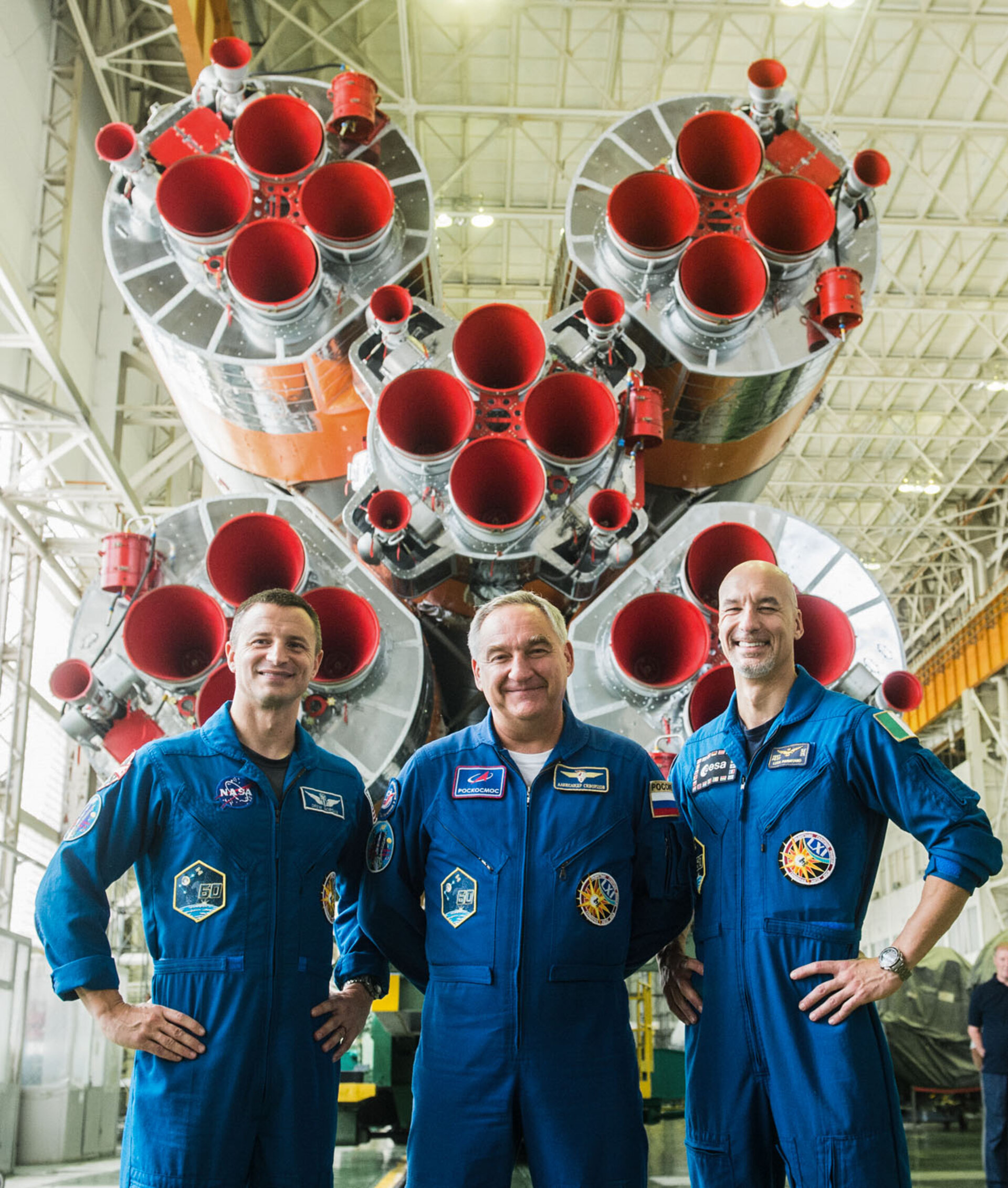 Members of Expedition 60 pose with their Soyuz launcher