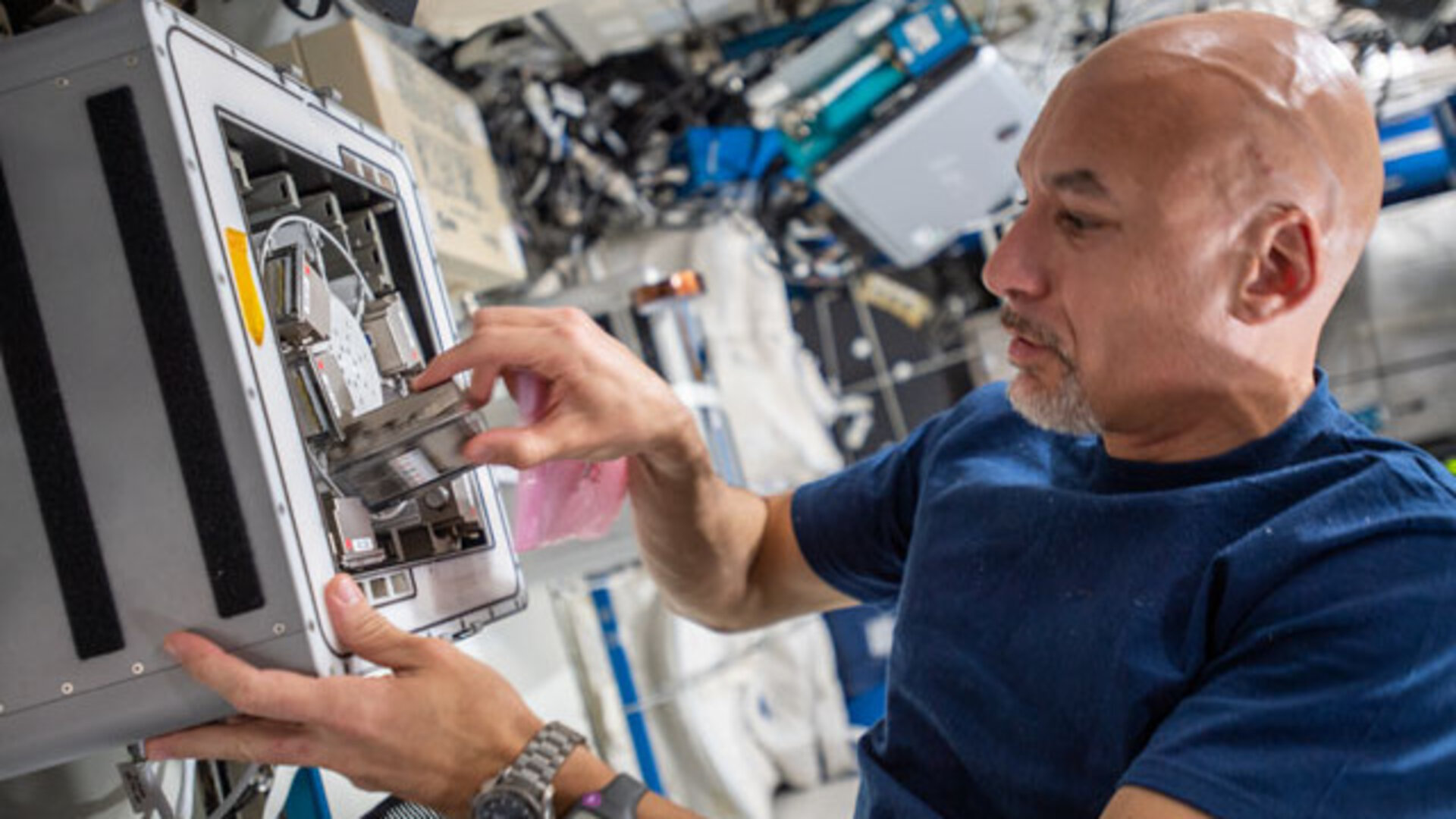 ESA astronaut Luca Parmitano installs a device to test how biofilms grow in altered gravity conditions
