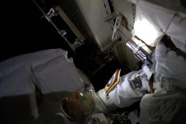 Luca removes fasteners by helmet light during first AMS spacewalk
