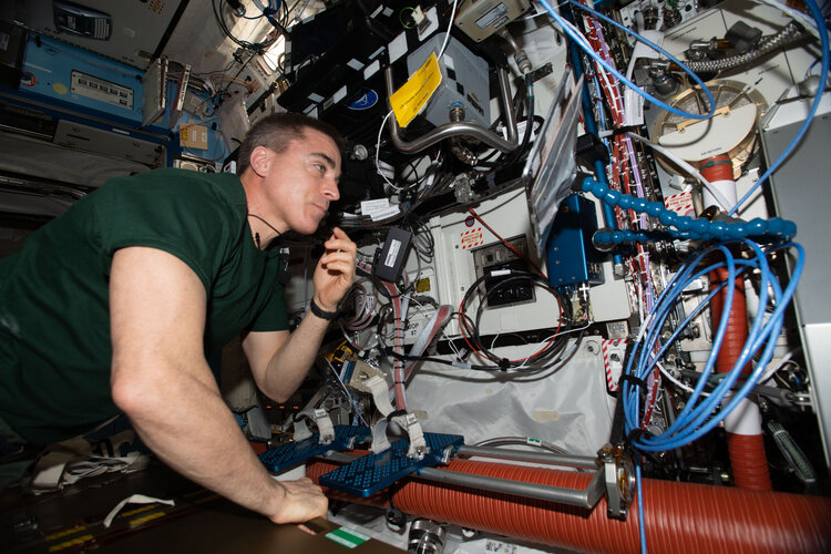 NASA astronaut and Expedition 63 Commander Chris Cassidy swaps a hard disk drive during computer maintenance on the robotics work station which controls and commands the Canadarm2 robotic arm.