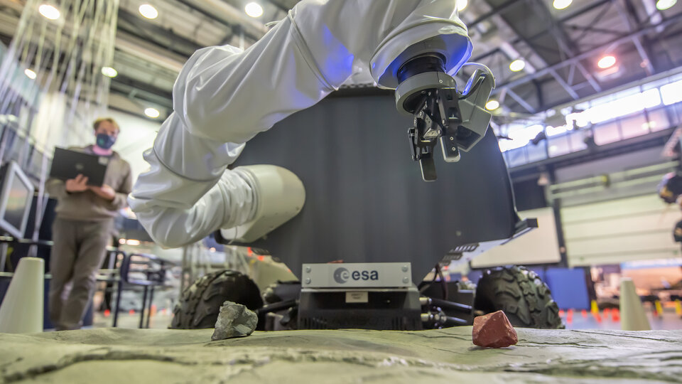 Interact rover picking up geological sample